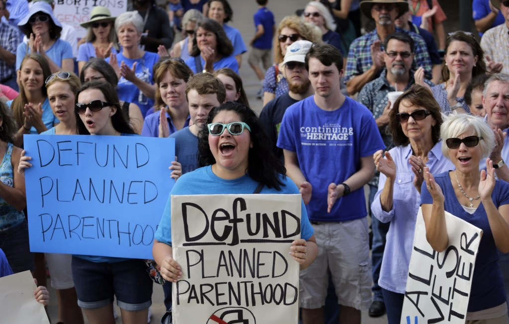 Erica Canaut, center, cheers as she and other anti-abortion activists rally on the steps of the Texas Capitol to condemn the use in medical research of tissue samples obtained from aborted fetuses, Tuesday, July 28, 2015, in Austin, Texas. (AP Photo/Eric Gay)